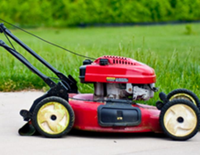 A red lawn mower on the sidewalk
