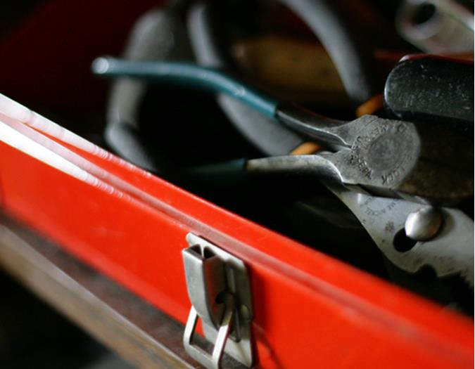 A red tool box with tools in it