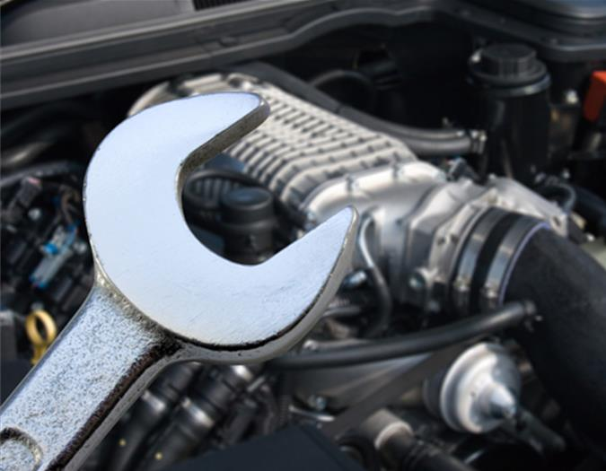 A silver wrench in front of a car engine