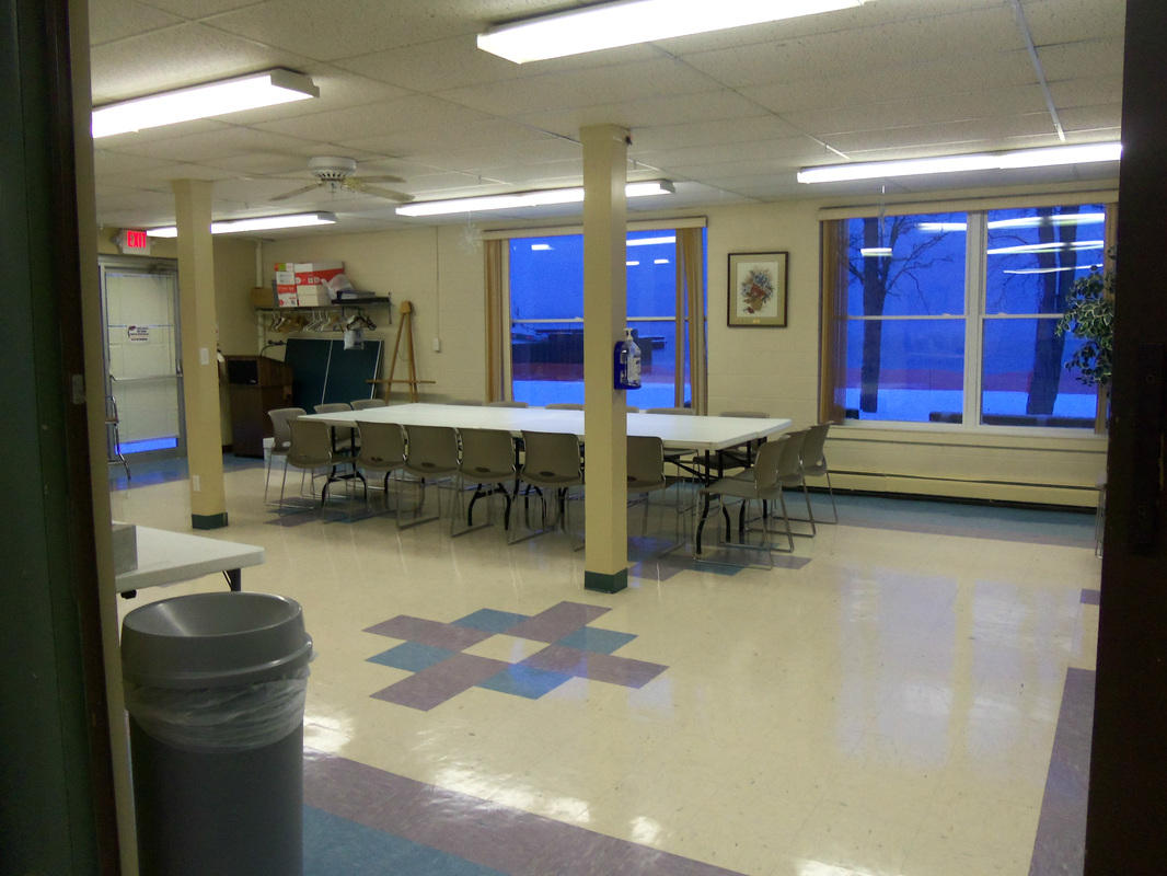An open space with windows and a long table