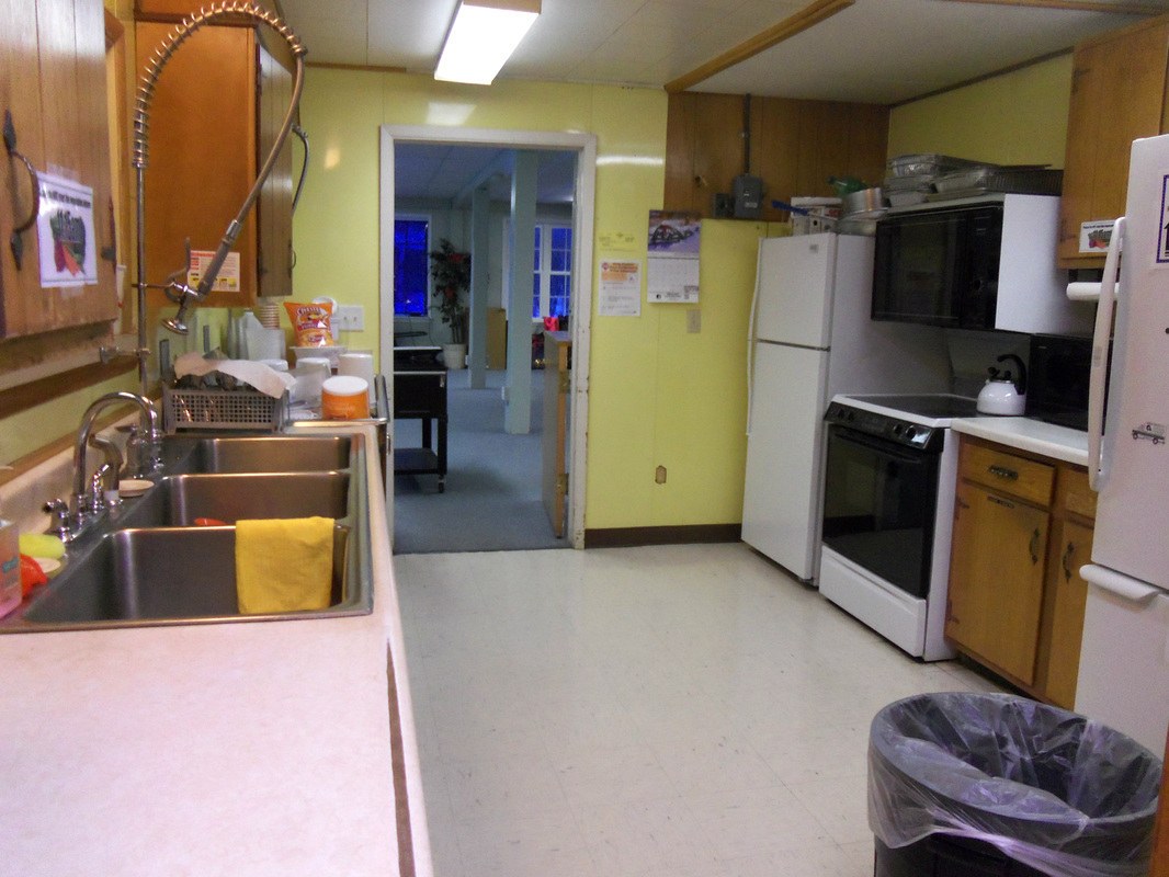 A kitchen with appliances and yellow walls