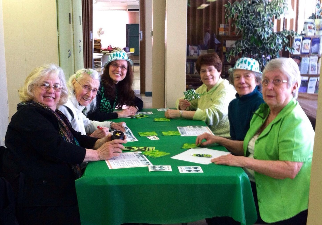 A group of women at a green table with green decorations