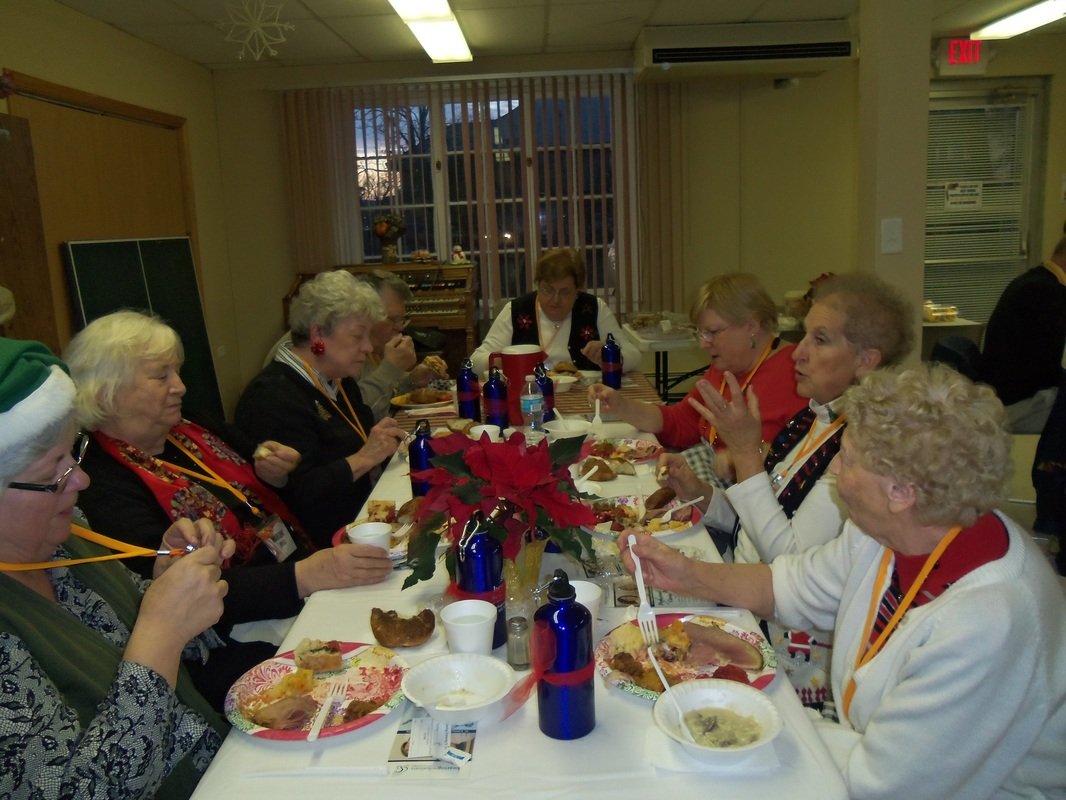 Ladies sitting at a table eating and talking at Christmas time