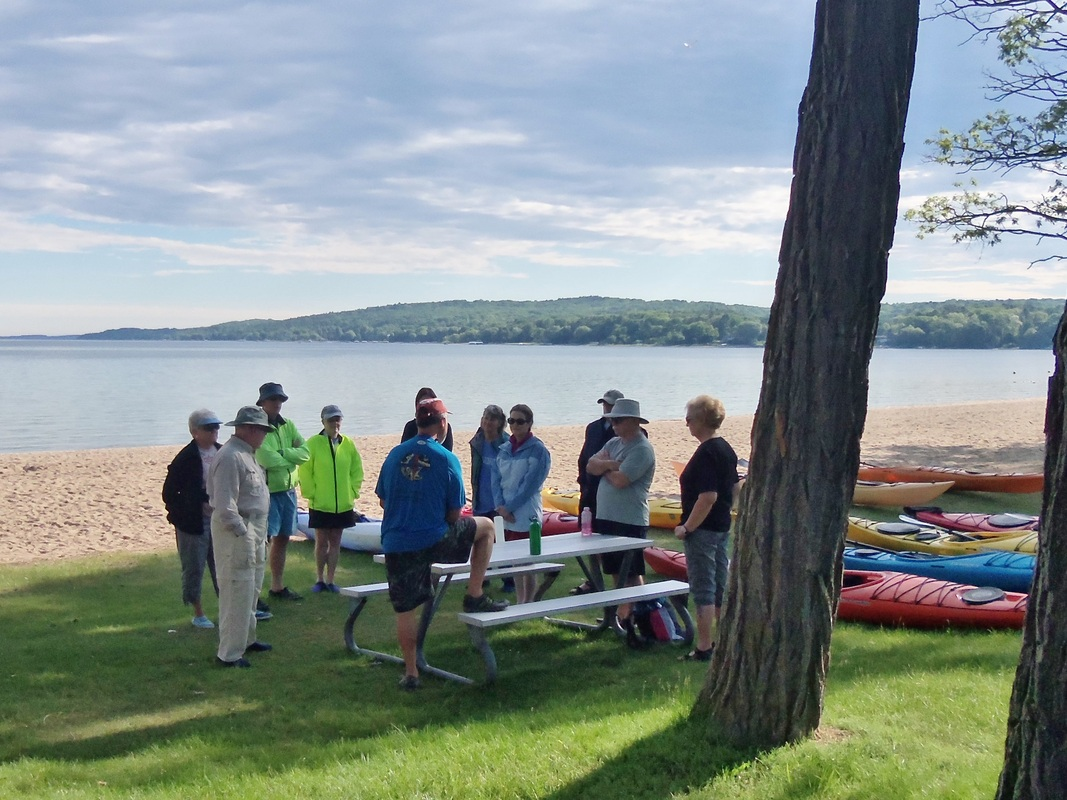 Men and women meeting at a picnic table next to kayaks by the water